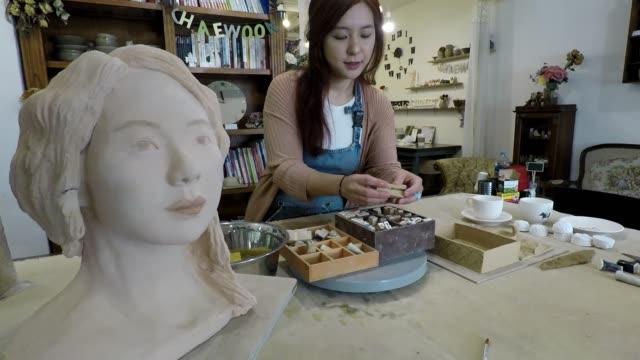 Korean woman artist working in her studio in Seoul video