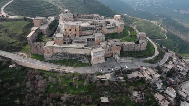 Krak des Chevaliers castle in Syria. Wonderful medieval castle on the top of a mountain in ruins after syrian war - aerial view with a drone Aerial view with a drone of Krak des Chevaliers castle in Syria. Wonderful medieval castle on the top of a mountain in ruins after syrian war damascus stock videos & royalty-free footage