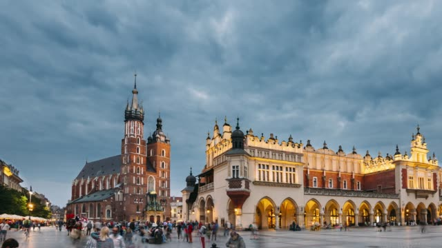 krakow, poland. night view of st. mary's basilica and cloth hall building. famous old landmark church of our lady assumed into heaven. unesco world heritage site - польша стоковые видео и кадры b-roll