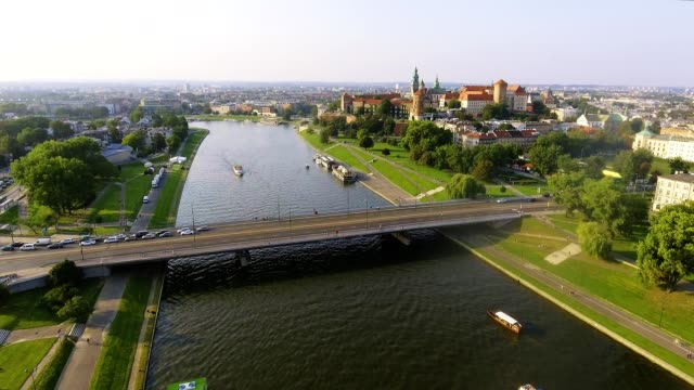 krakow, poland. wawel royal castle and cathedral, vistula river. aerial flyby video at sunrise in summer - польша стоковые видео и кадры b-roll