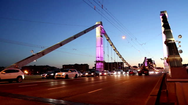 krymsky bridge or crimean bridge and traffic of cars (night)-- is a steel suspension bridge in moscow, russia. the bridge spans the moskva river 1,800 metres south-west from the kremlin - rzeka moskwa filmów i materiałów b-roll