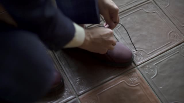 Kuchl / Austria - August 23 2019: Morning  groom's preparations, man in tuxedo puts on shoes, ties shoelaces. Businessman getting ready. Wedding ceremony. Accessories, details. Slow motion close-up
