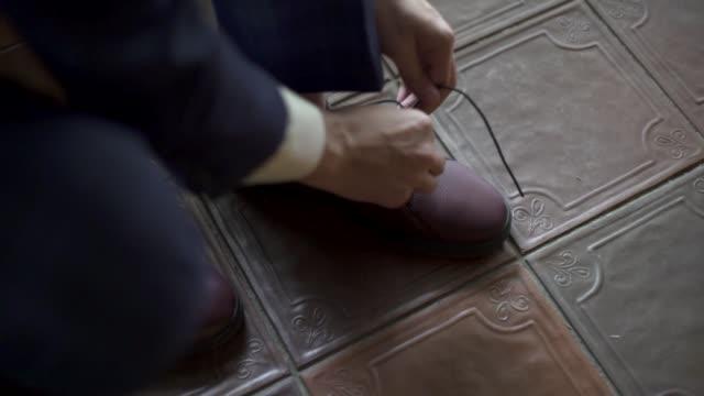 kuchl / austria - 23 sierpnia 2019: poranne przygotowania pana młodego, mężczyzna w smokingu zakłada buty, wiąże sznurowadła. biznesmen przygotowuje się. ślub. akcesoria, szczegóły. zbliżenie w zwolnionym tempie - para aranżacja filmów i materiałów b-roll