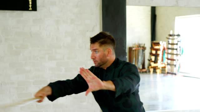 vídeos de stock, filmes e b-roll de kung fu fighter pratica artes marciais com chicote enfiar 4k - autodefesa