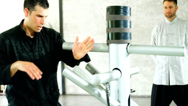 vídeos de stock, filmes e b-roll de lutador de kung fu, praticar artes marciais com o manequim de madeira 4k - autodefesa