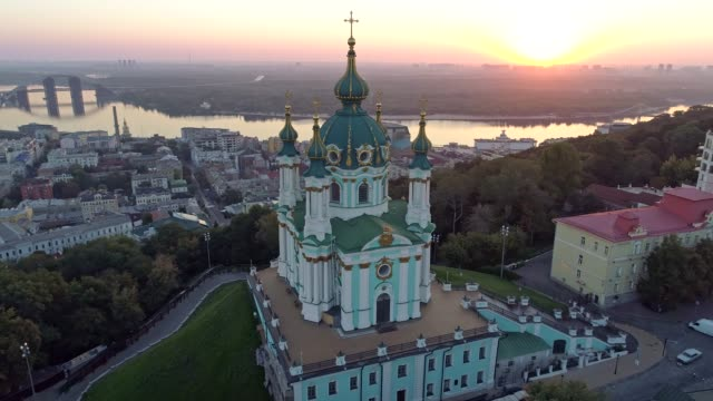 kyiv, ukraine. flying around st. andrew's church of ecumenical patriarchate, orthodox church during sunrise. view of podil and dnieper river. aerial shot, 4k - barocco video stock e b–roll
