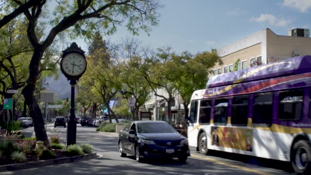 La Crescenta-Montrose Main Street Establishing Shot with Clock Cars and busses transport people down Honolulu St. in Montrose California on a sunny afternoon. Screen left is the new clock that was recently added. b roll stock videos & royalty-free footage