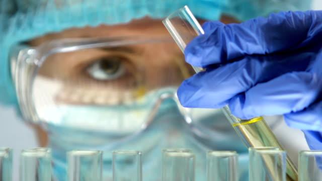 лабораторный эксперт, добавляя химическое вещество в образец мочи в пробирке, проверка здоровья - expert стоковые видео и кадры b-roll