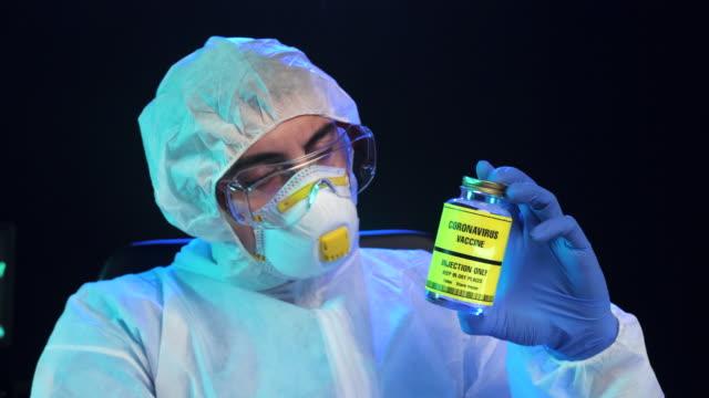 laboratuvarda coronavirus aşı şişesi gösteren laboratuvar bilim adamı, pozitif duygu, yavaş hareket - covid vaccine stok videoları ve detay görüntü çekimi