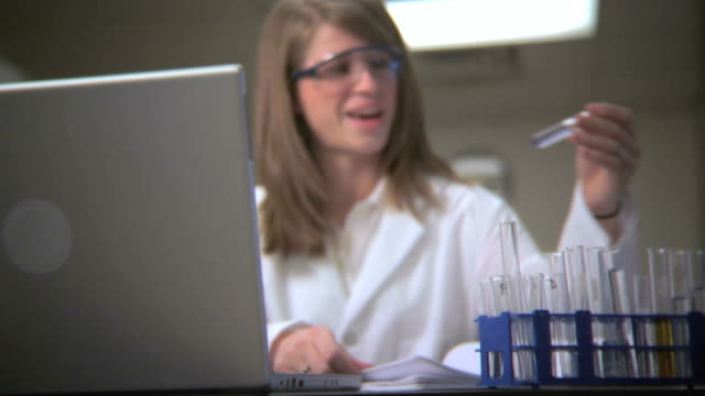 Lab technician analyzing test tubes video