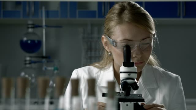 Lab technician doing microscope sample analysis video