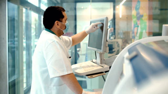 lab technician entering data into a blood analyzer. - covid ospedale video stock e b–roll