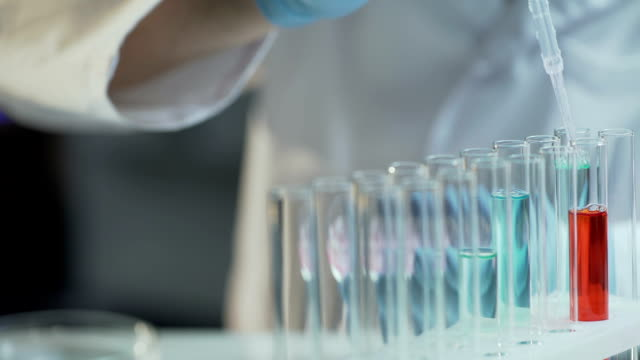 Lab worker adding concentrate to different reagents to follow reactions dynamics video