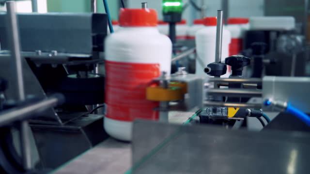 Labeled plastic bottles are moving along the conveyor and getting marked
