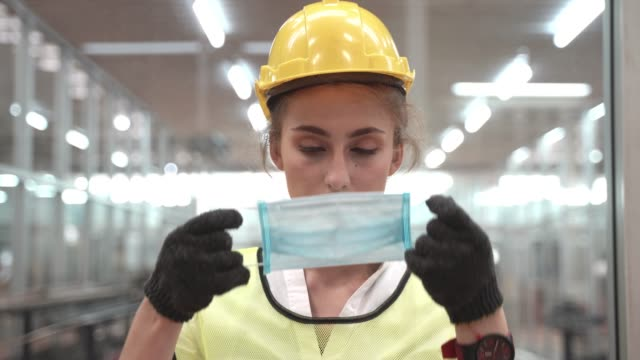 labor woman worker is wearing protection mask face and safety helmet and wearing suit green reflective safety dress in high tech clean factory. concept of smart industry worker operating. - bezpieczeństwo filmów i materiałów b-roll