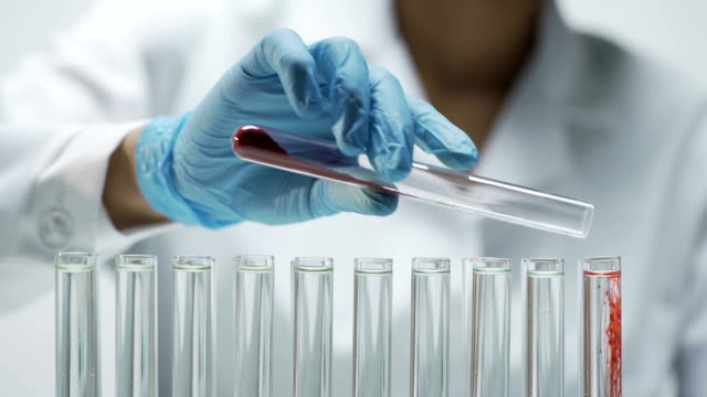 Laboratorian adding dry test material into tubes, conducting research in lab video