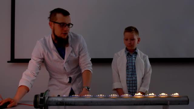 vídeos de stock, filmes e b-roll de assistente de laboratório com rapaz faz experiências com altifalante ardente - música acústica