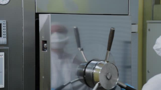 dipendente laboratorio apre autoclave per sterilizzazione - autoclave video stock e b–roll