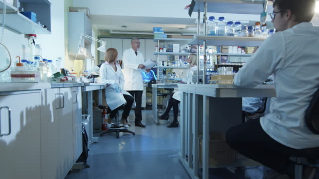 Laboratory scientists in white coats are having a celebration at work. video