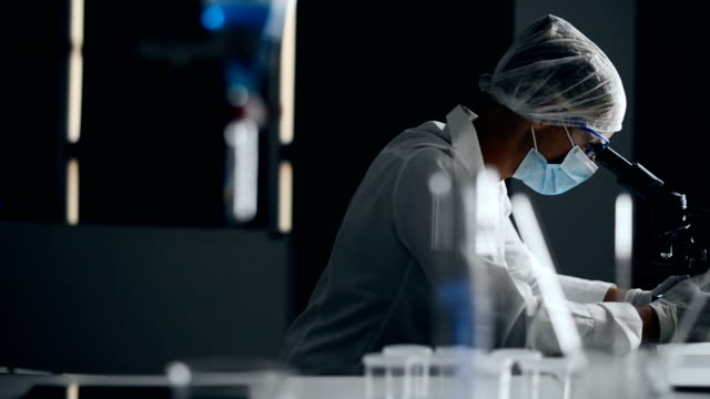 Laboratory technician Female laboratory technician working late night in the lab. microscope stock videos & royalty-free footage