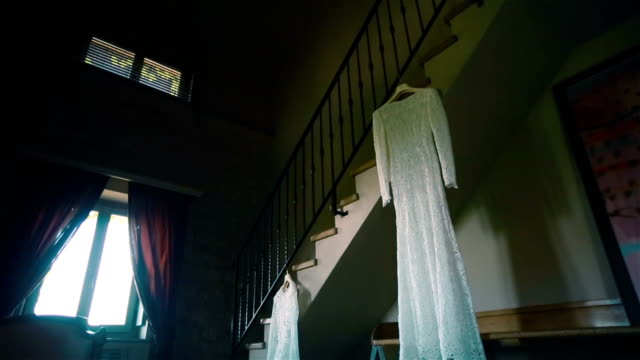 Lace wedding dress hanging on ladder in antique room and waiting for bride. Pan Lace wedding dress hanging on ladder in antique room and waiting for bride. Pan 19th century style stock videos & royalty-free footage
