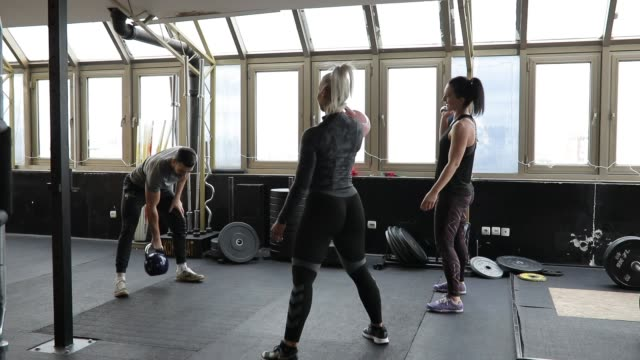 Ladies exercising with personal trainer in gym
