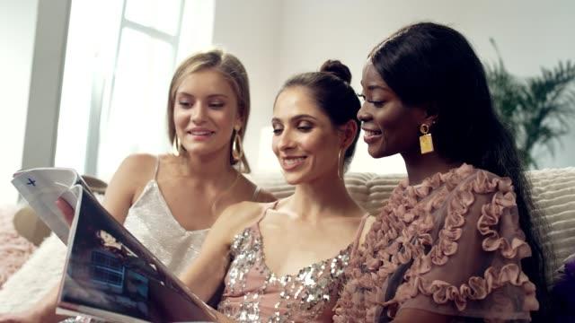 stockvideo's en b-roll-footage met ladies nacht plezier. multi etnische vrienden lezen magazine - woman home magazine