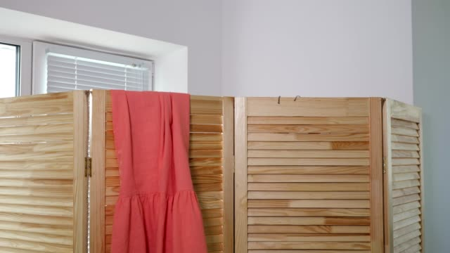 lady changes clothes and hangs on wooden screen in boutique