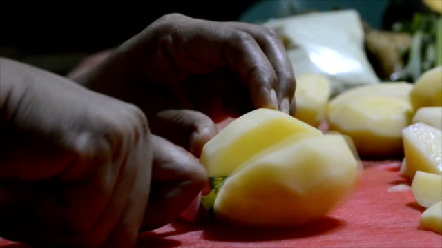 lady cook chopping peeled potato with knife on chopping board with dirty finger nails - patate video stock e b–roll