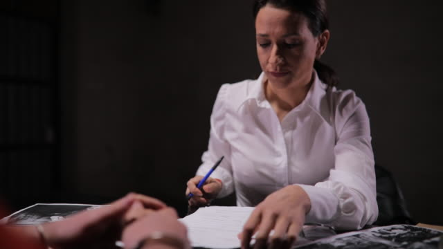 Lady detective interrogating a prisoner Woman detective interrogating a man prisoner in dark investigation room. police interview stock videos & royalty-free footage