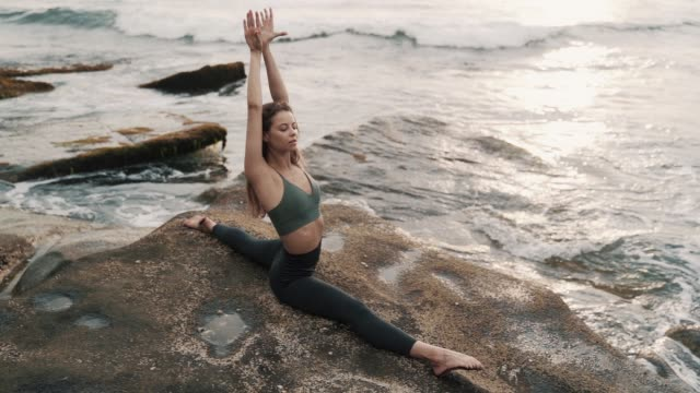 lady does longitudinal twine sitting on rock against ocean lady with nice figure does longitudinal twine sitting on volcanic rock against ocean surfs with sunset reflection slow motion doing the splits stock videos & royalty-free footage