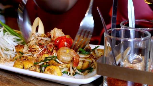 vidéos et rushes de dame mangeant la nourriture thaïlandaise célèbre appelée pad thai recette - fourchette