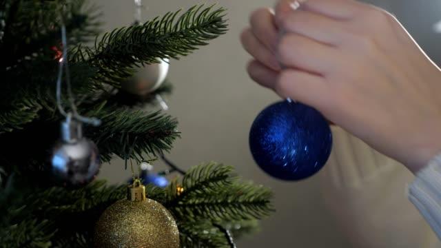 signora tiene decorazioni natalizie e indossa albero artificiale - decorare video stock e b–roll