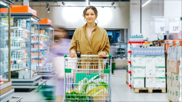 lady in brown coat stands with shopping cart at fridges - vídeo