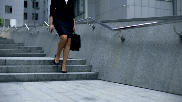 Lady in business suit walking downstairs from office center, end of working day video