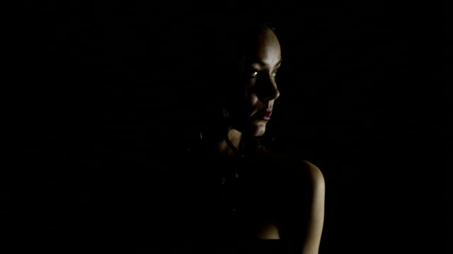 Lady in dramatic light Dramatic light on beautiful mysterious brunette low lighting stock videos & royalty-free footage