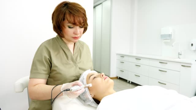 lady in green coat makes microdermabrasion procedure on face - kosmetyczka praca w salonie piękności filmów i materiałów b-roll