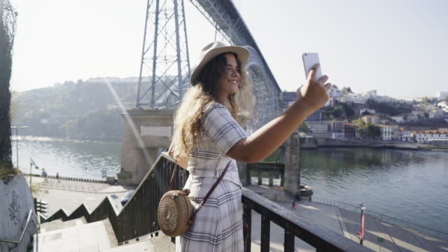 lady in hat taking selfie on smartphone on embankment - portogallo video stock e b–roll