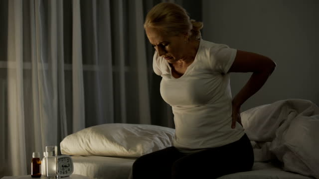 vídeos de stock e filmes b-roll de lady in her 50 cannot sleep due to acute pain in lower back and kidneys, health - dor