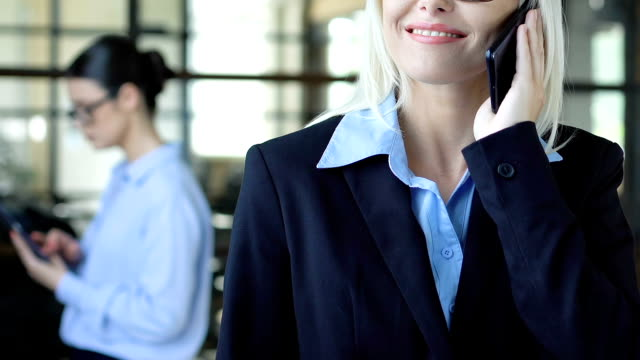 Lady in suit listening client on phone, consulting services, business solutions