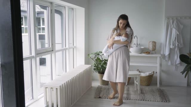 pani w letniej sukience trzyma dziecko w ramionach i karmi piersią - aktywny tryb życia filmów i materiałów b-roll