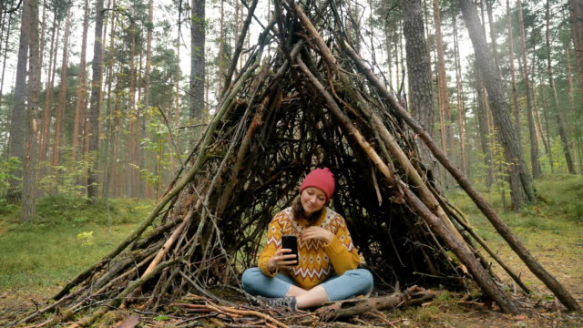 Lady in sweater uses mobile phone sitting inside hut in wood