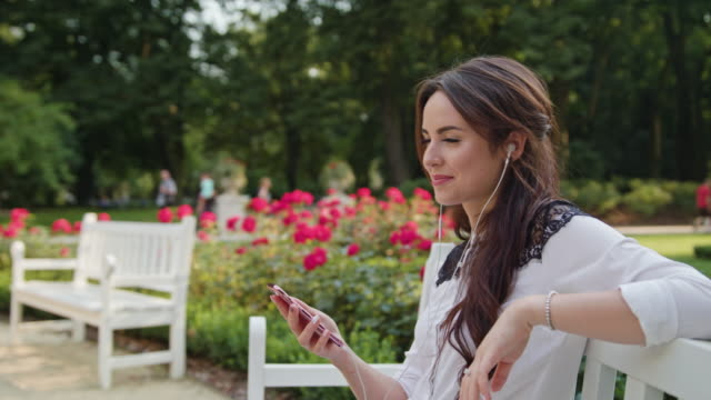 Lady in the Park Listening to Music on the Phone video