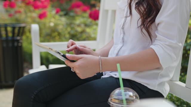 Señora en el Parque usando una tableta - vídeo