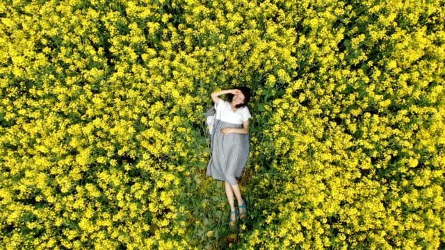 lady in white and grey summer dress lies on blooming field - leżeć filmów i materiałów b-roll