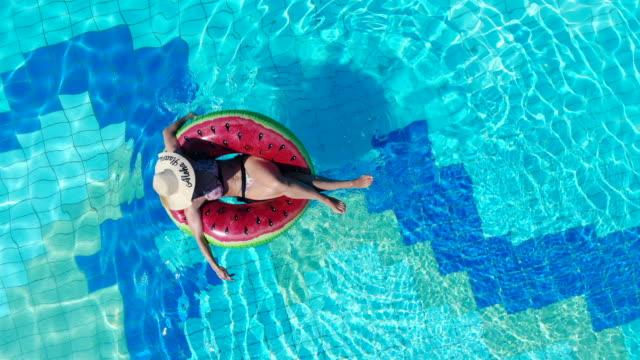 vídeos de stock, filmes e b-roll de uma dama está flutuando pela piscina. conceito das férias de verão. - boia salva vidas