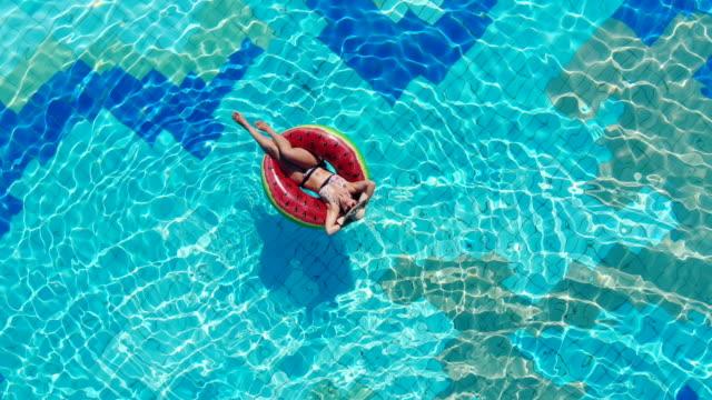 stockvideo's en b-roll-footage met een dame ligt op een zwem ring in het zwembad. zorgeloze dame tijdens de zomervakantie. - opblaasband