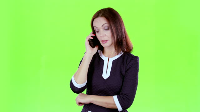 Lady is talking on the phone with her daughters. Green screen video
