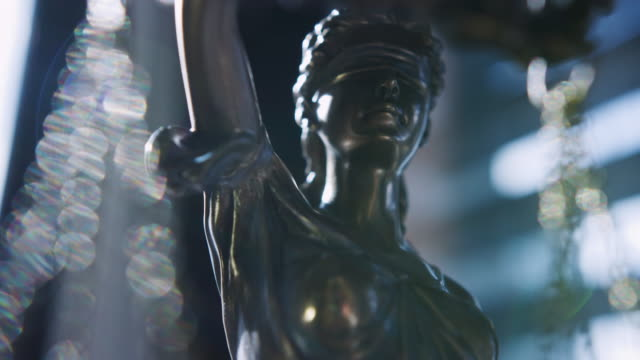 Lady Justice blindfolded and holding balance scales and a sword. Crime, Justice, Court and Law Concepts. RED Camera, Slow motion