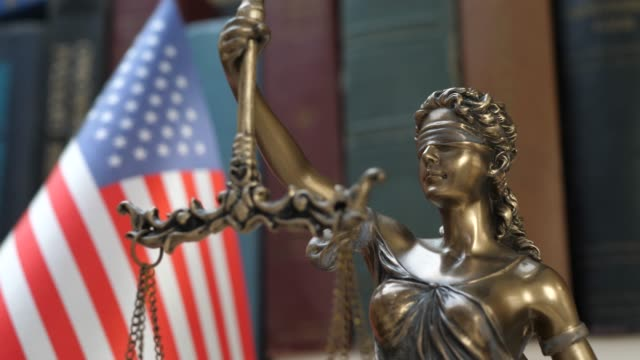 Lady Justice Symbol with USA Flag and Bookshelf Background